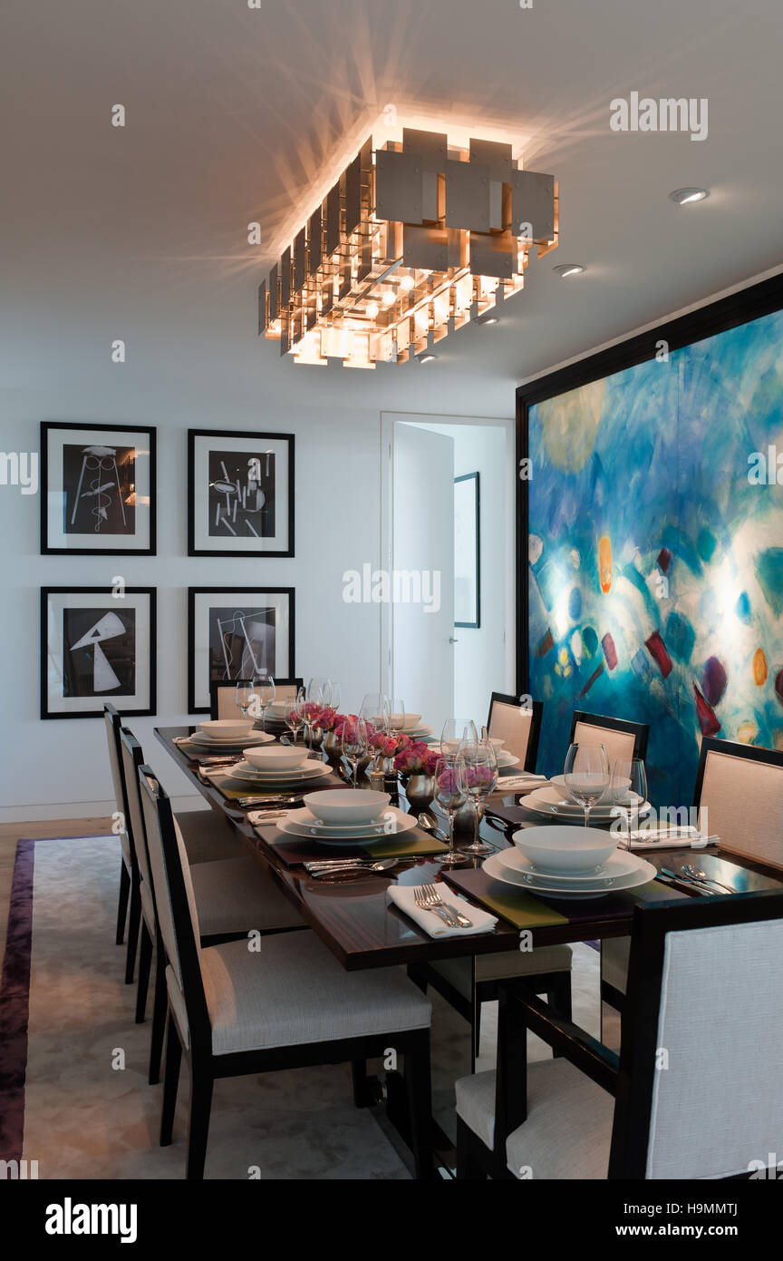 Dining table with large modern art canvas in flat by Collett-Zarzycki,  property development by Richard Rogers, - Stock Image