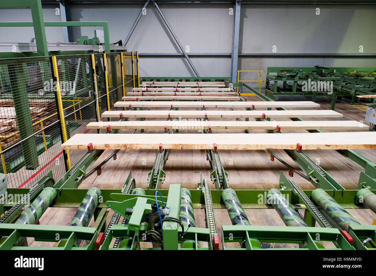 Wooden planks on machinery in timber processing plant, Templin, Uckermark district of Brandenurg, Germany. - Stock Image