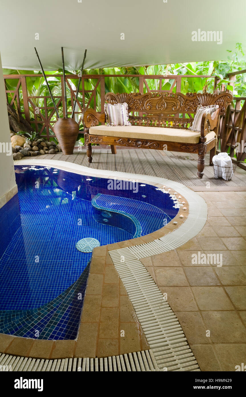 Carved bench and plunge pool in Santa Lucia, spa resort, hotel and therapy centre, Caribbean - Stock Image