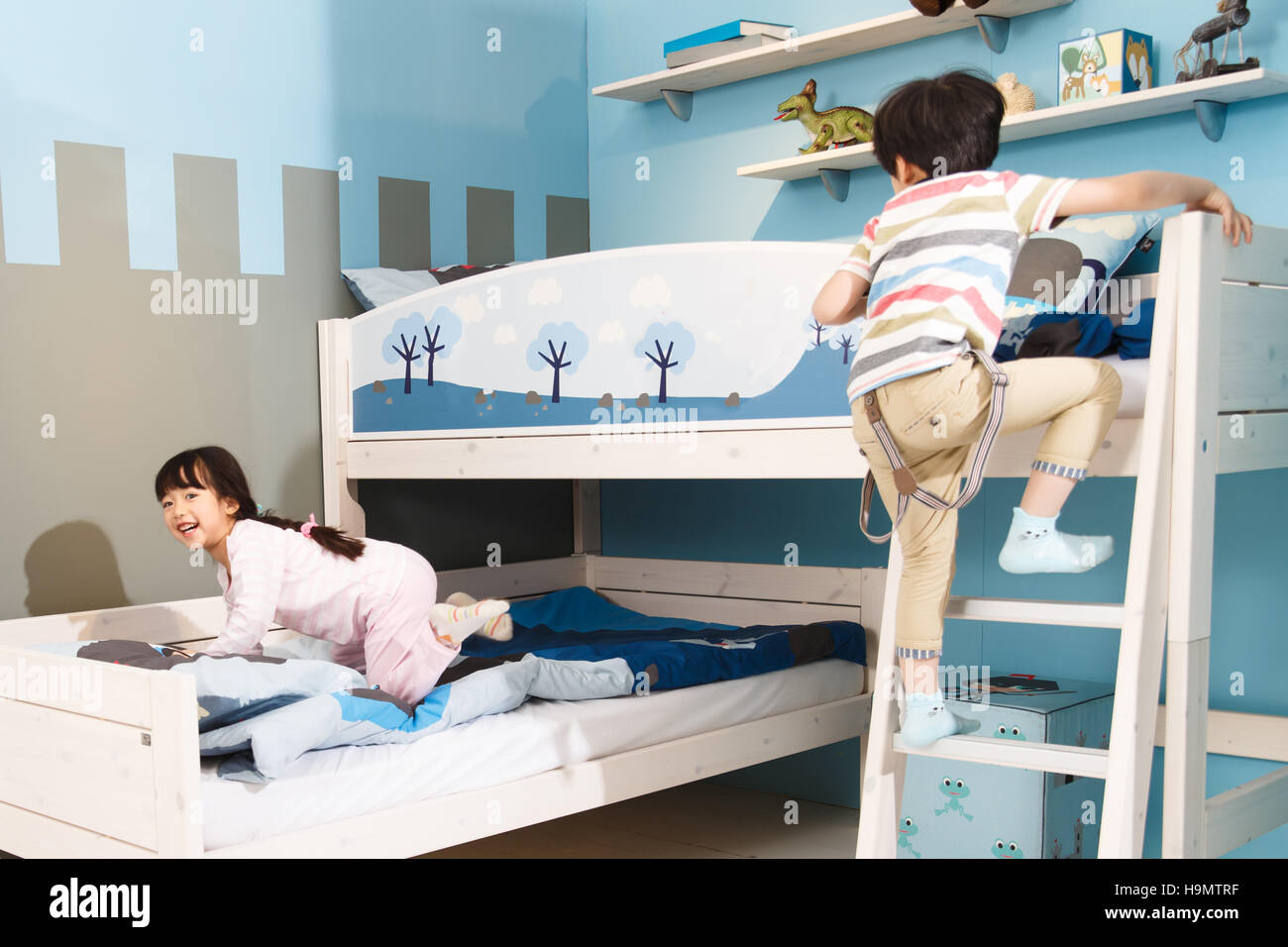 Two children play in a bunk bed. - Stock Image