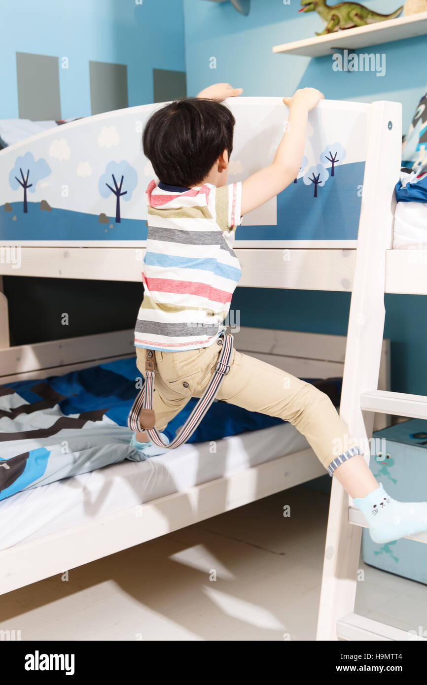 Cute little boy playing in the bedroom - Stock Image