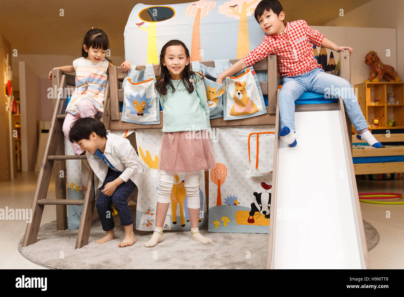 Happy children play on the bed - Stock Image