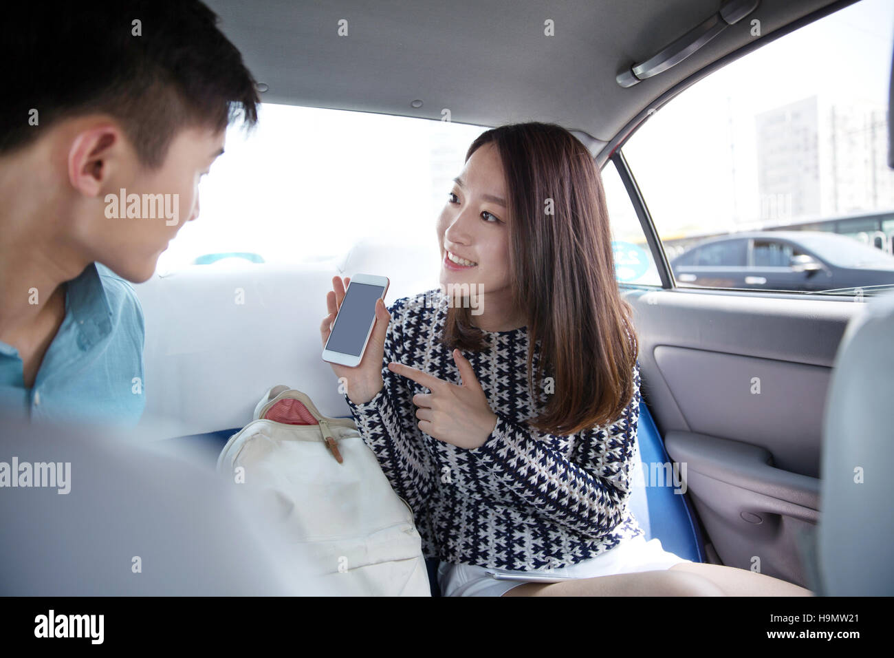 Young lovers in the car holding a mobile phone navigation - Stock Image
