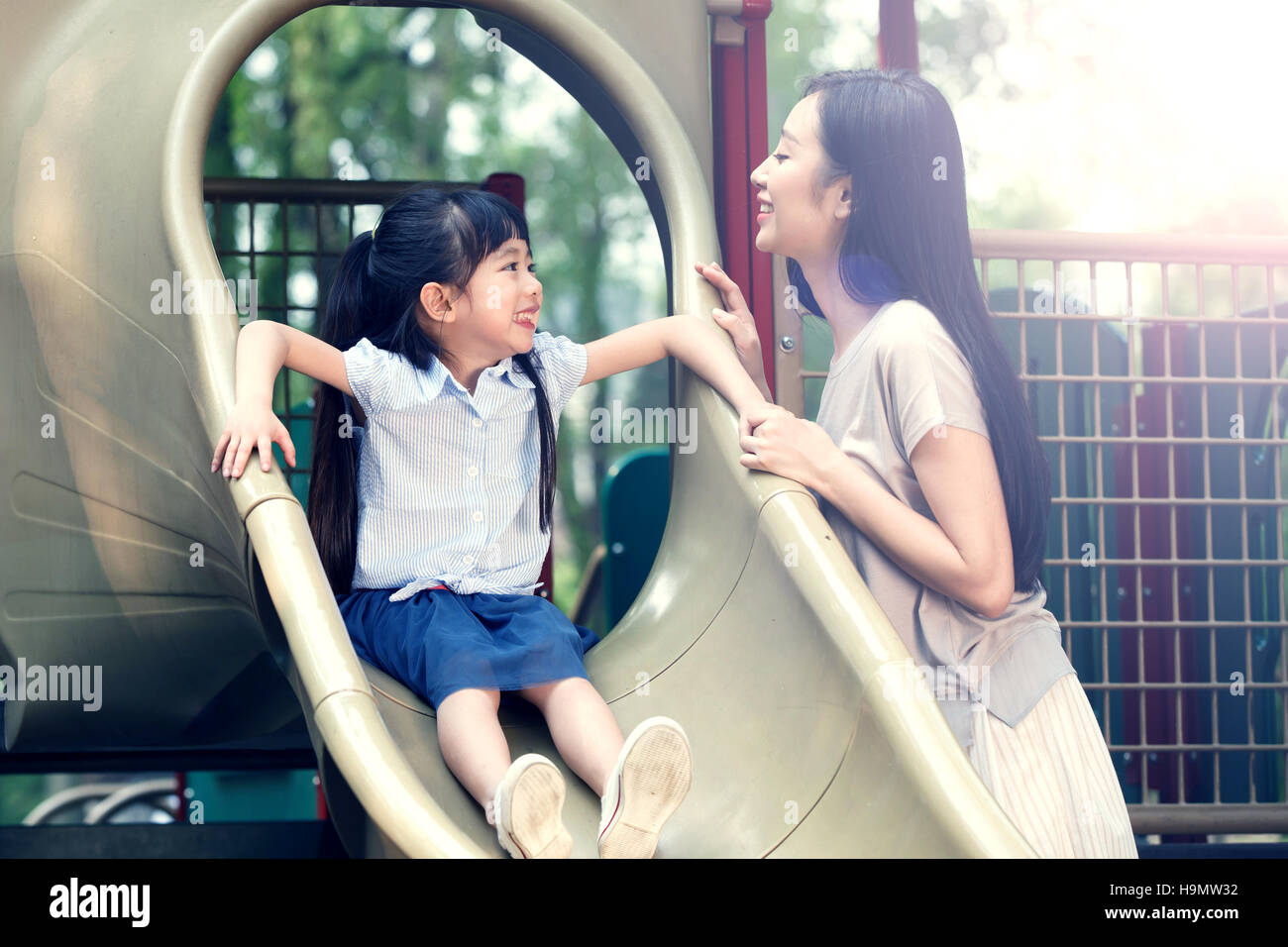 Mother to accompany the girl slide - Stock Image