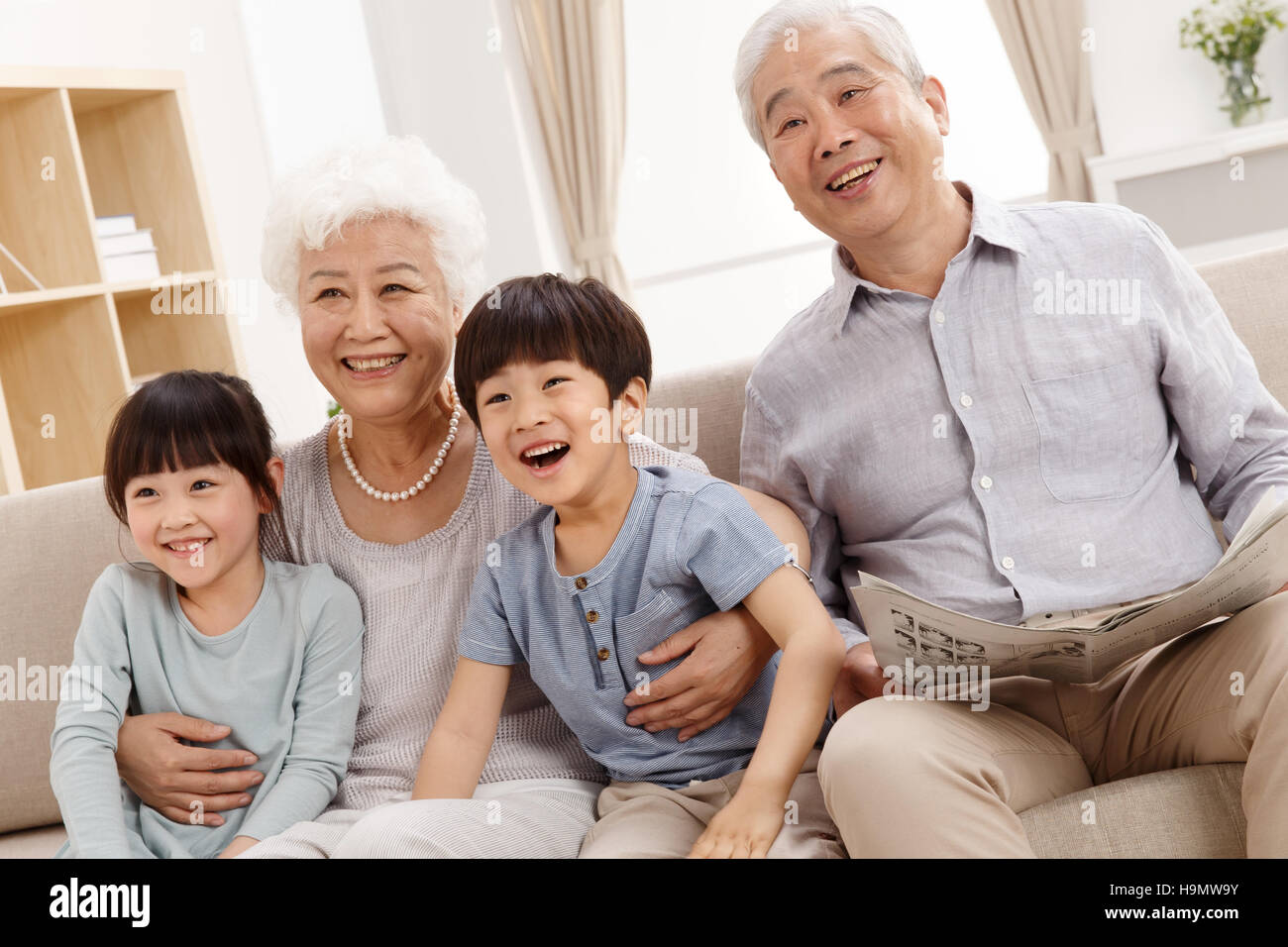 Happy family watching TV in the living room - Stock Image