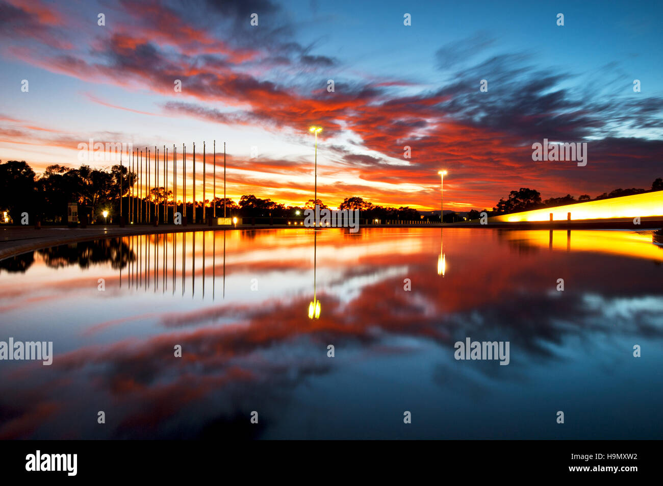 Sunrise reflections in the fountain at the front of Canberra's Parliament. - Stock Image
