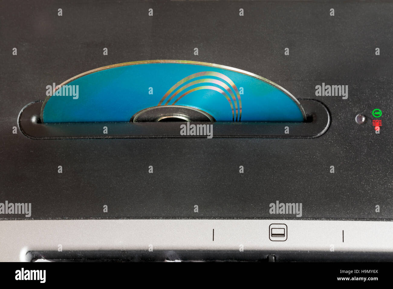 Compact disc inserted in shredder to destroy sensitive information - Stock Image
