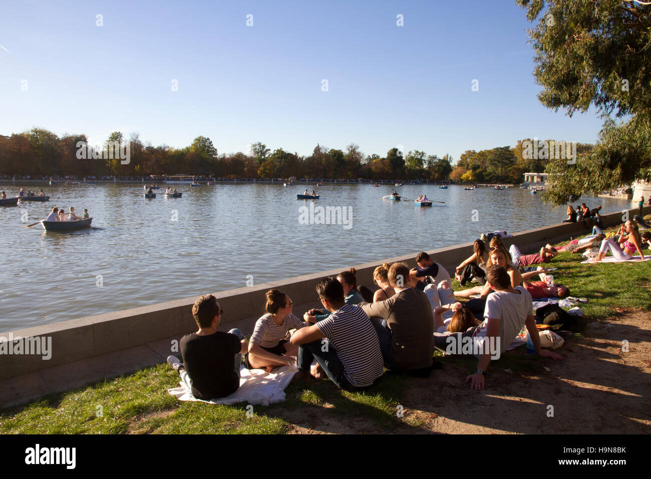 Madrid Spain Park of Retiro tourists visiting day lake scene young sitting on sun in a sunny day - Stock Image