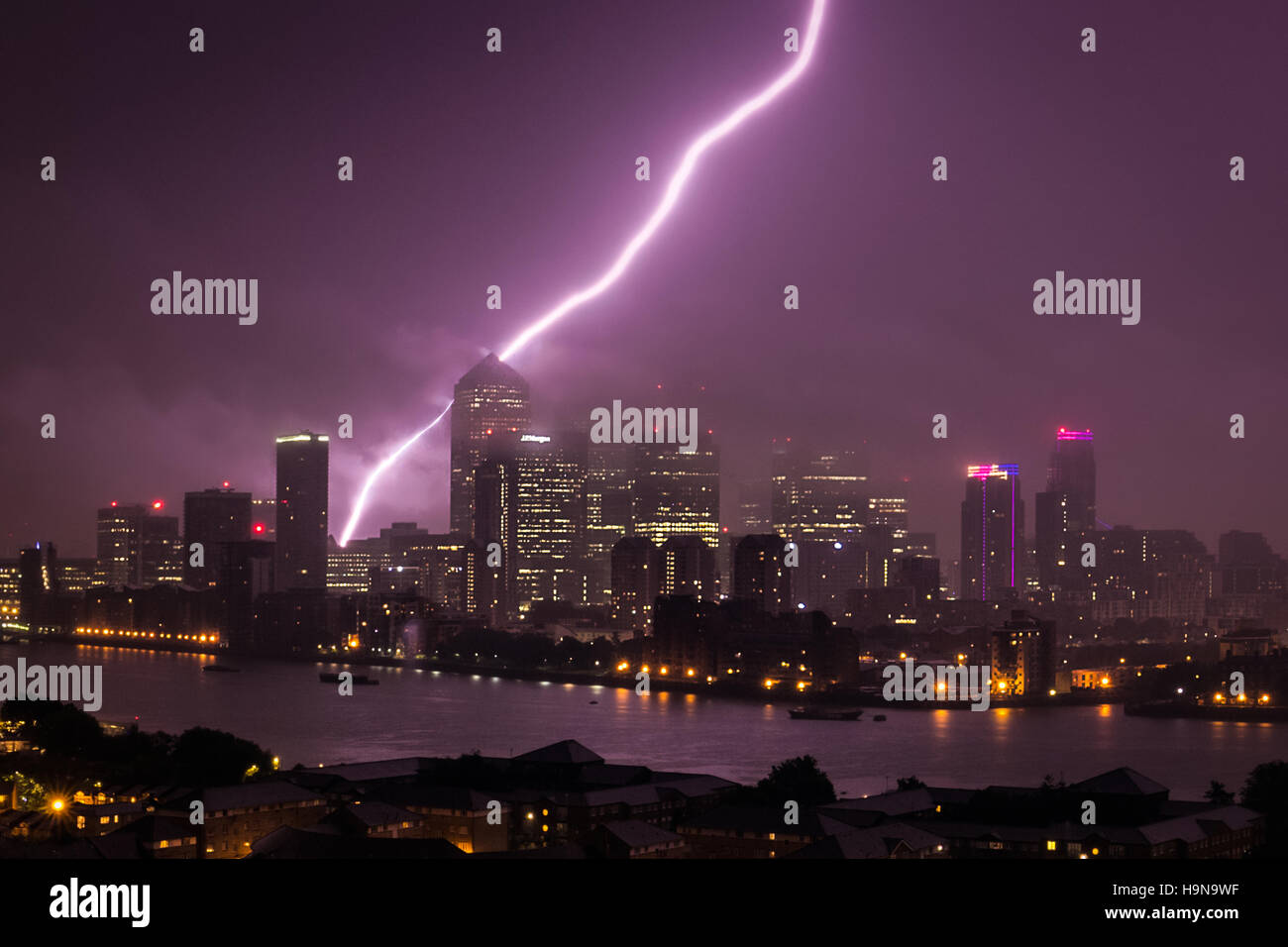 Massive Lightning strike just behind Canary Wharf business park buildings and River Thames in London, UK. Stock Photo