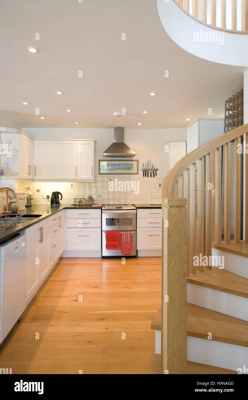 white kitchen with spiral staircase. Stock Photo