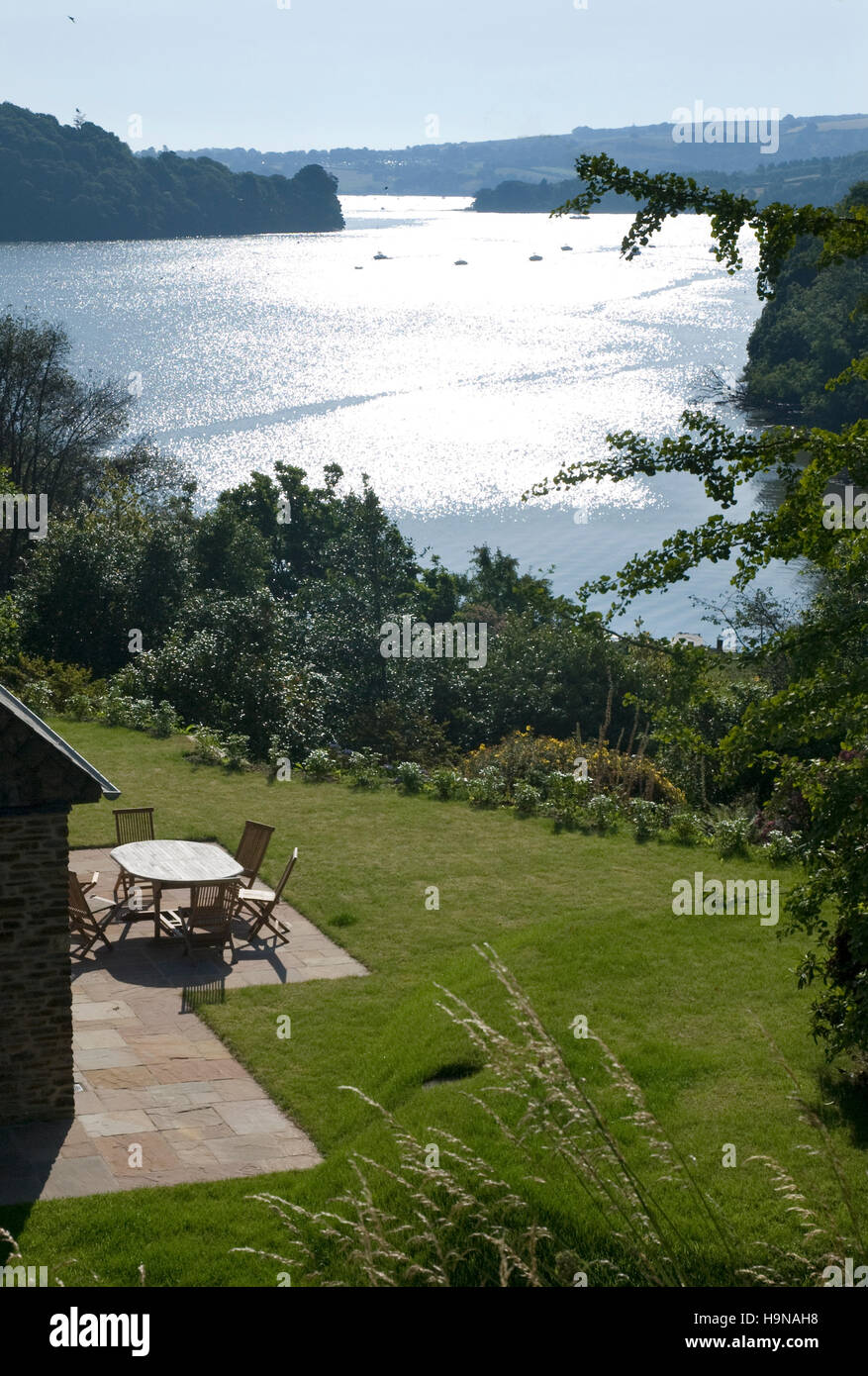 River view, estuary, water reflections, garden with furniture. sun on water Stock Photo