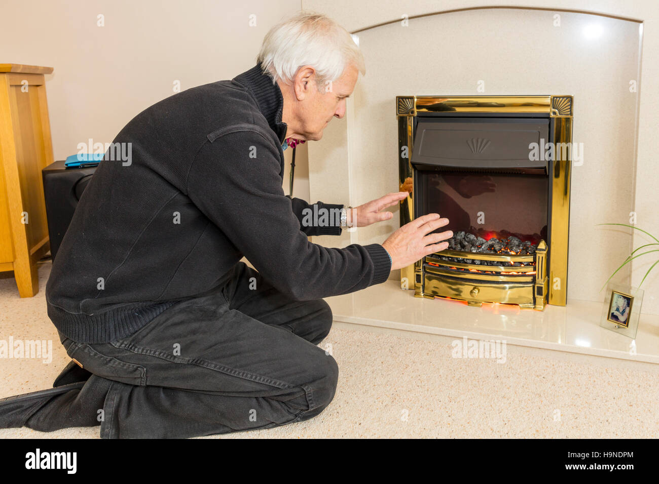 OAP trying to keep warm warming hands near fire keeping bills down cannot afford heating bill high gas energy bills - Stock Image