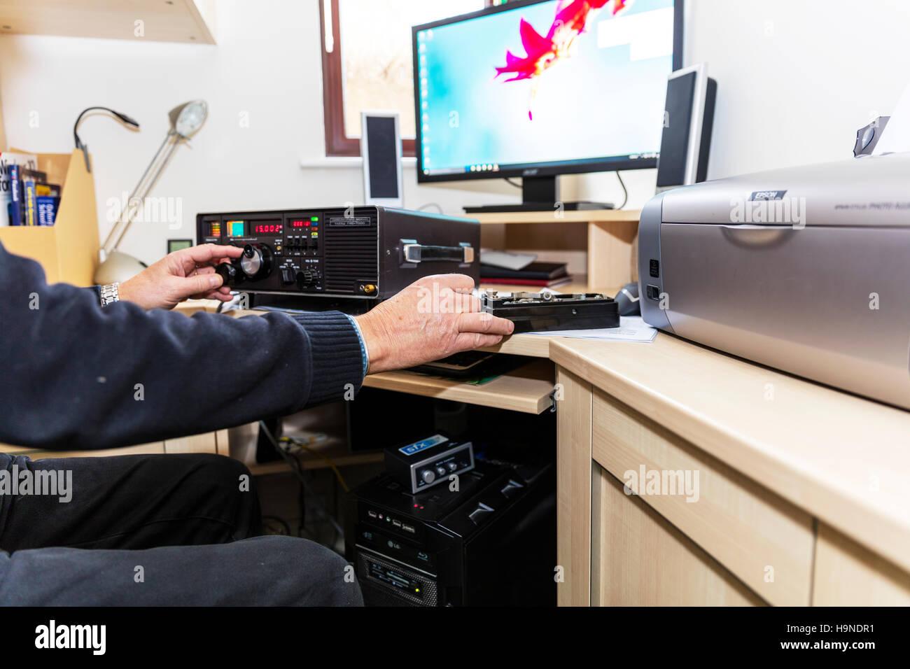 Using Morse key morse code Radio ham amateur radio enthusiast using Yaesu FRG 7000 High Frequency receiver changing - Stock Image