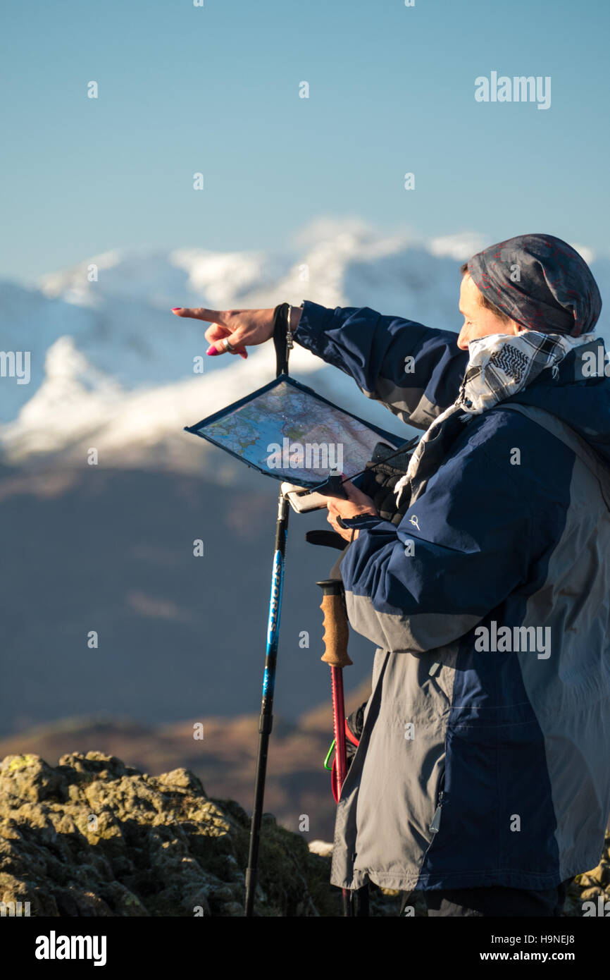 Woman looking at map and pointing which way to go - Stock Image