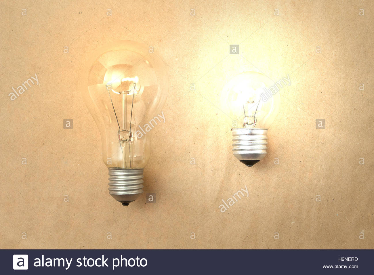 One Dim Light Bulb And Another Bright Light Bulb On Light Paper Background Idea