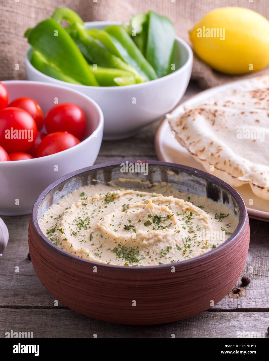 Humus in homemade bowl chapati, lemon and vegetable. - Stock Image