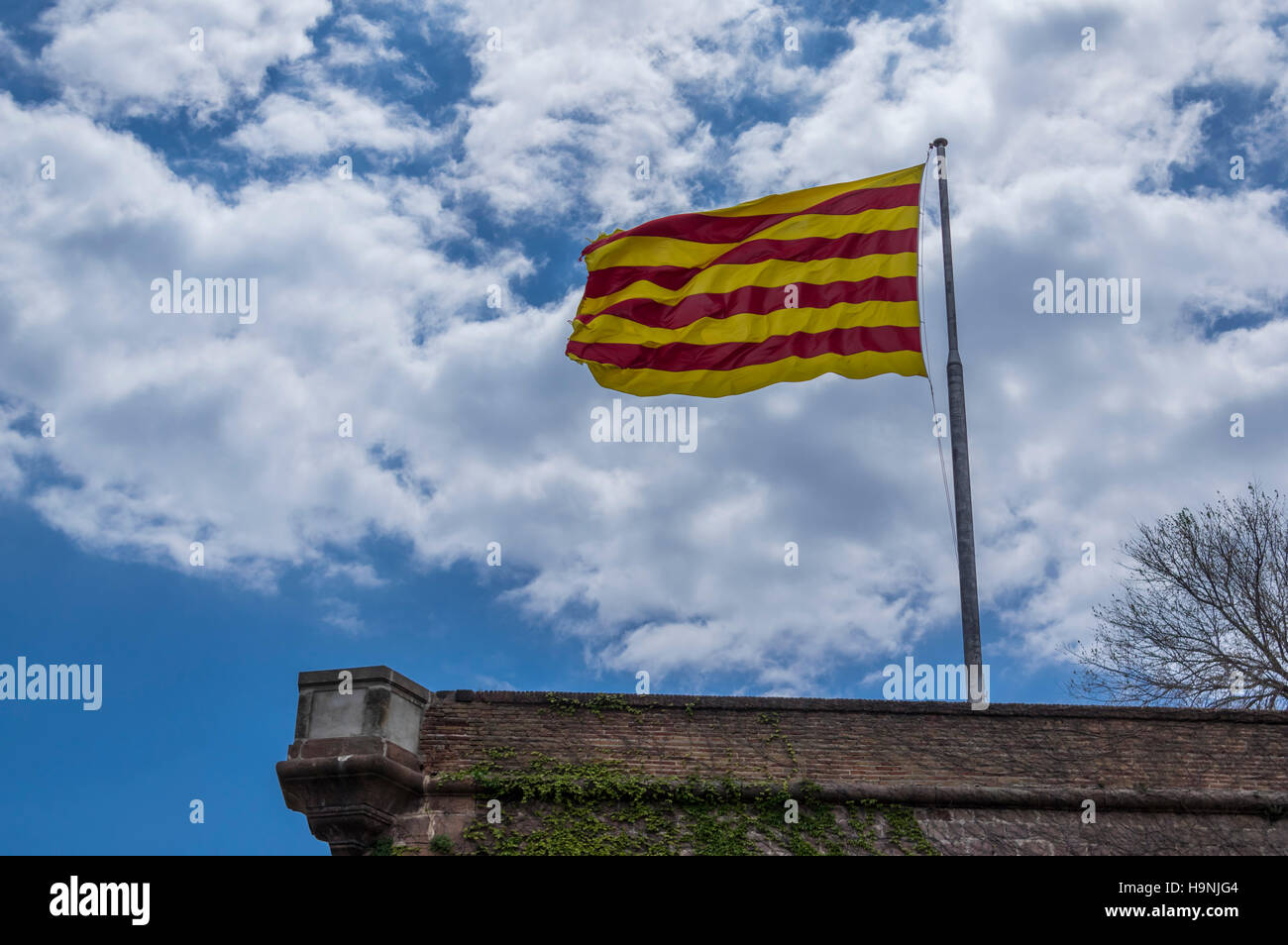 Worn out Catalan flag against blue sky and clouds. - Stock Image