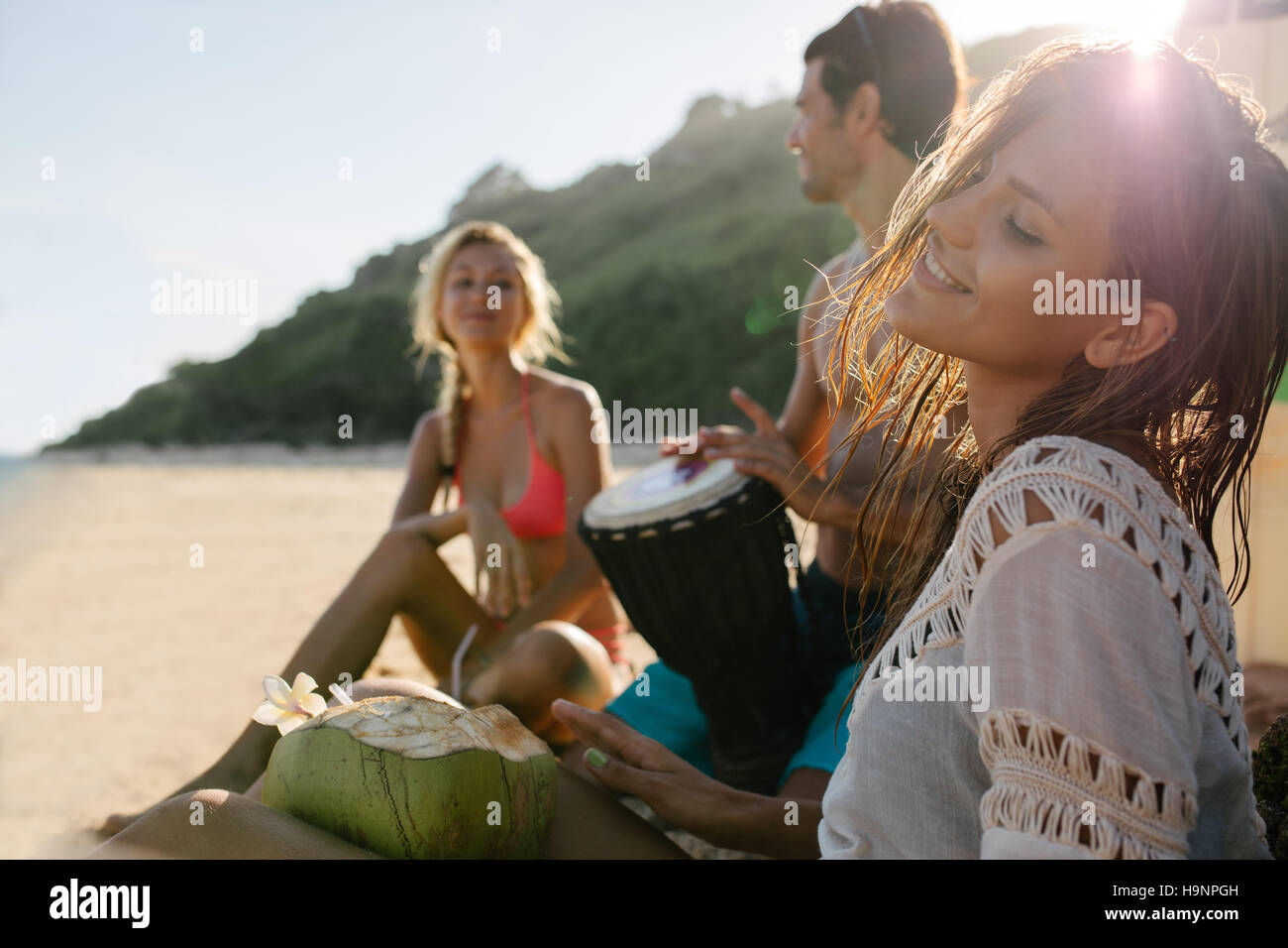 Young woman relaxing on the sea shore with her friends in background. Friends partying and having fun on the beach. - Stock Image