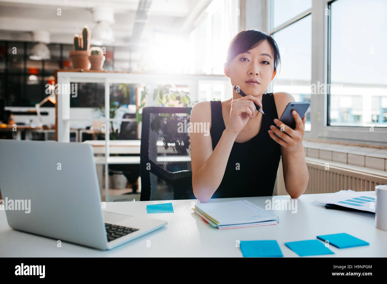 Portrait of confident asian woman sitting at her desk with mobile phone. Asian businesswoman working in office. - Stock Image