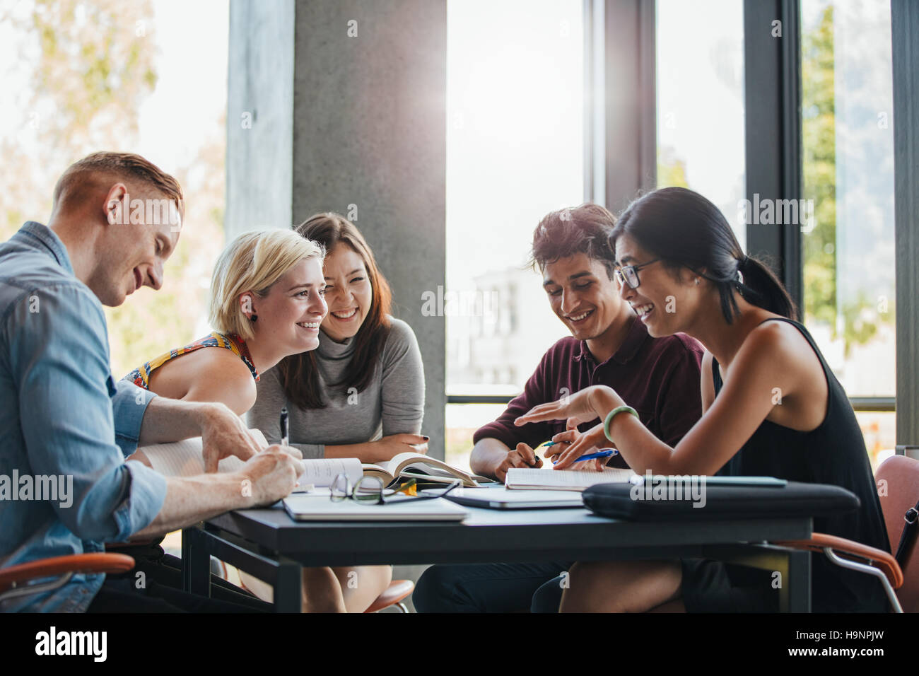 Happy young university students studying with books in library. Group of multiracial people in college library. - Stock Image