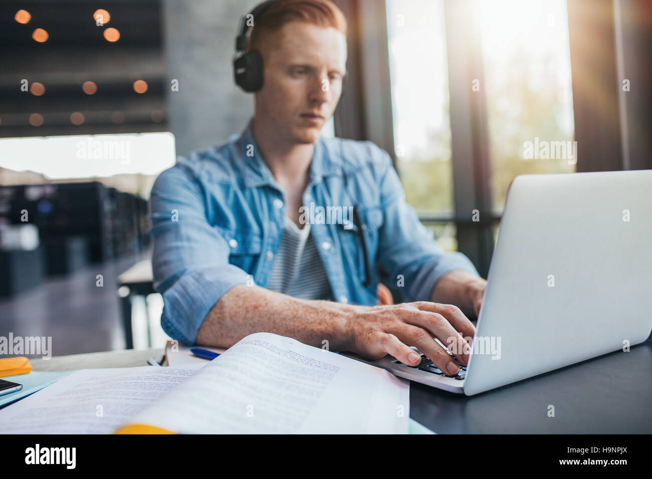 Male student in university library using laptop. Young man studying on school assignment. - Stock Image