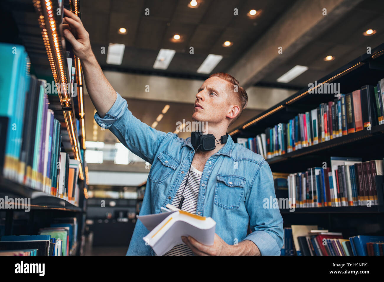 Shot of young male student selecting book from library shelf. University student studying in library. - Stock Image