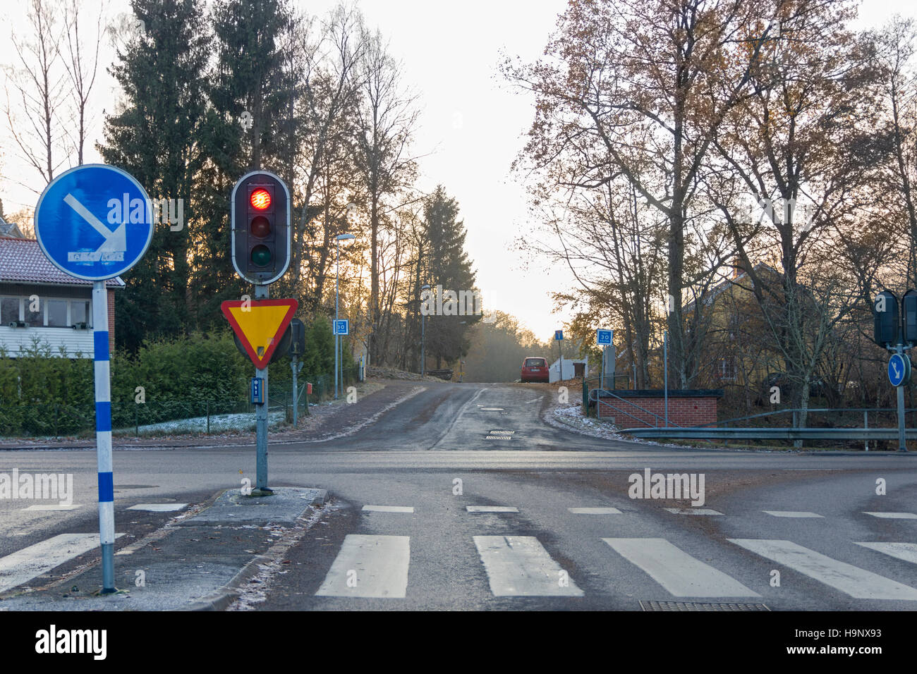 Street intersection with no traffic and traffic lights on red. Floda, Sweden  Model Release: No.  Property Release: - Stock Image