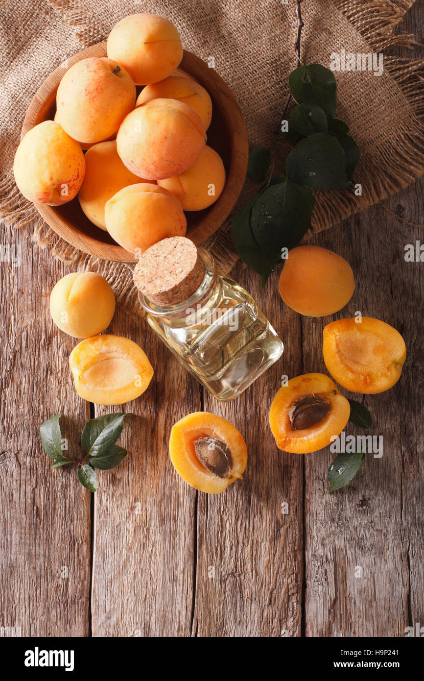 apricot kernel oil in a glass jar closeup on the table and ingredients. Vertical view from above - Stock Image
