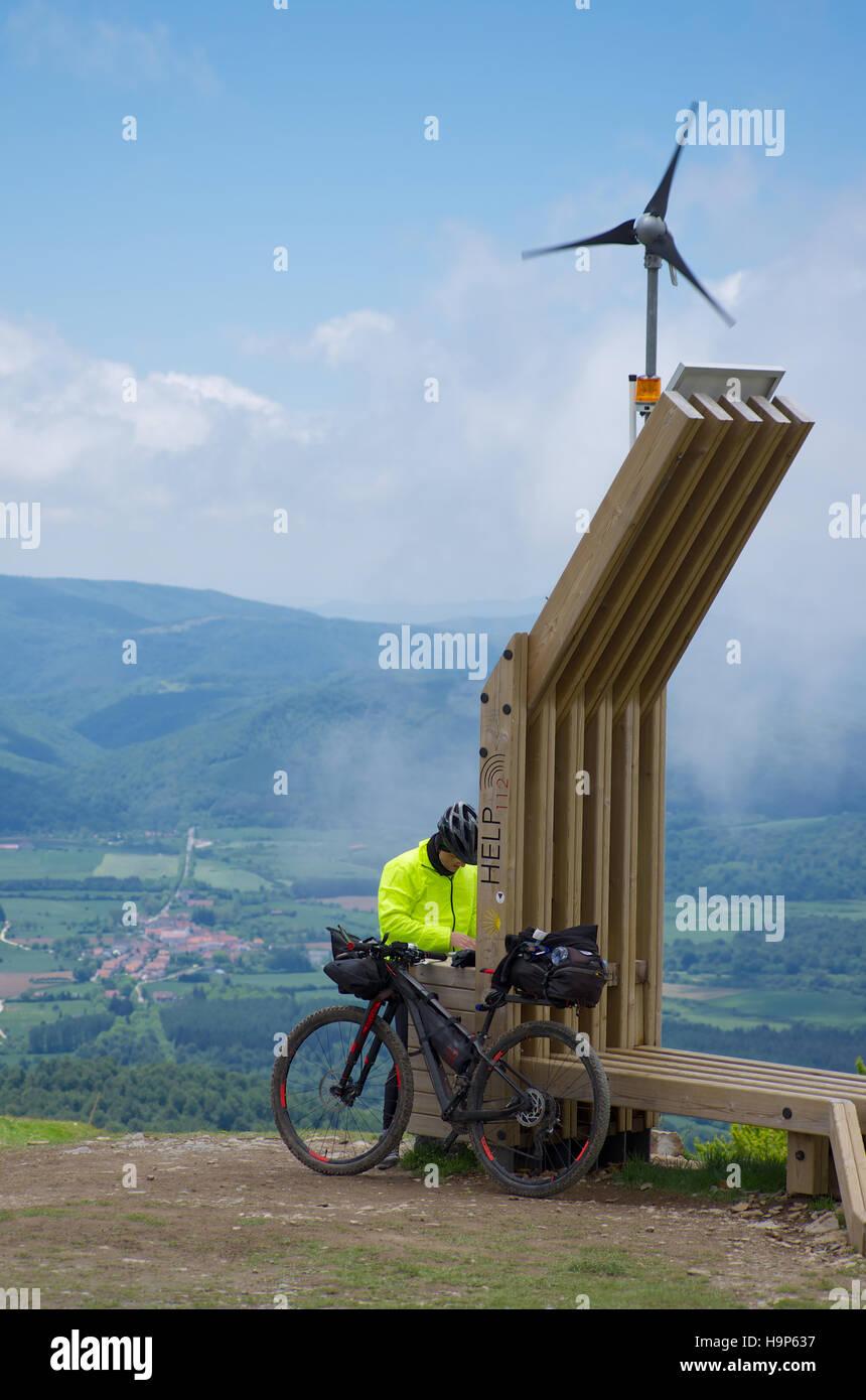 Cyclist pilgrim checking his route at Helpoint Lepoeder, Roncesvalles Pass, pilgrim route to Santiago de Compostela - Stock Image