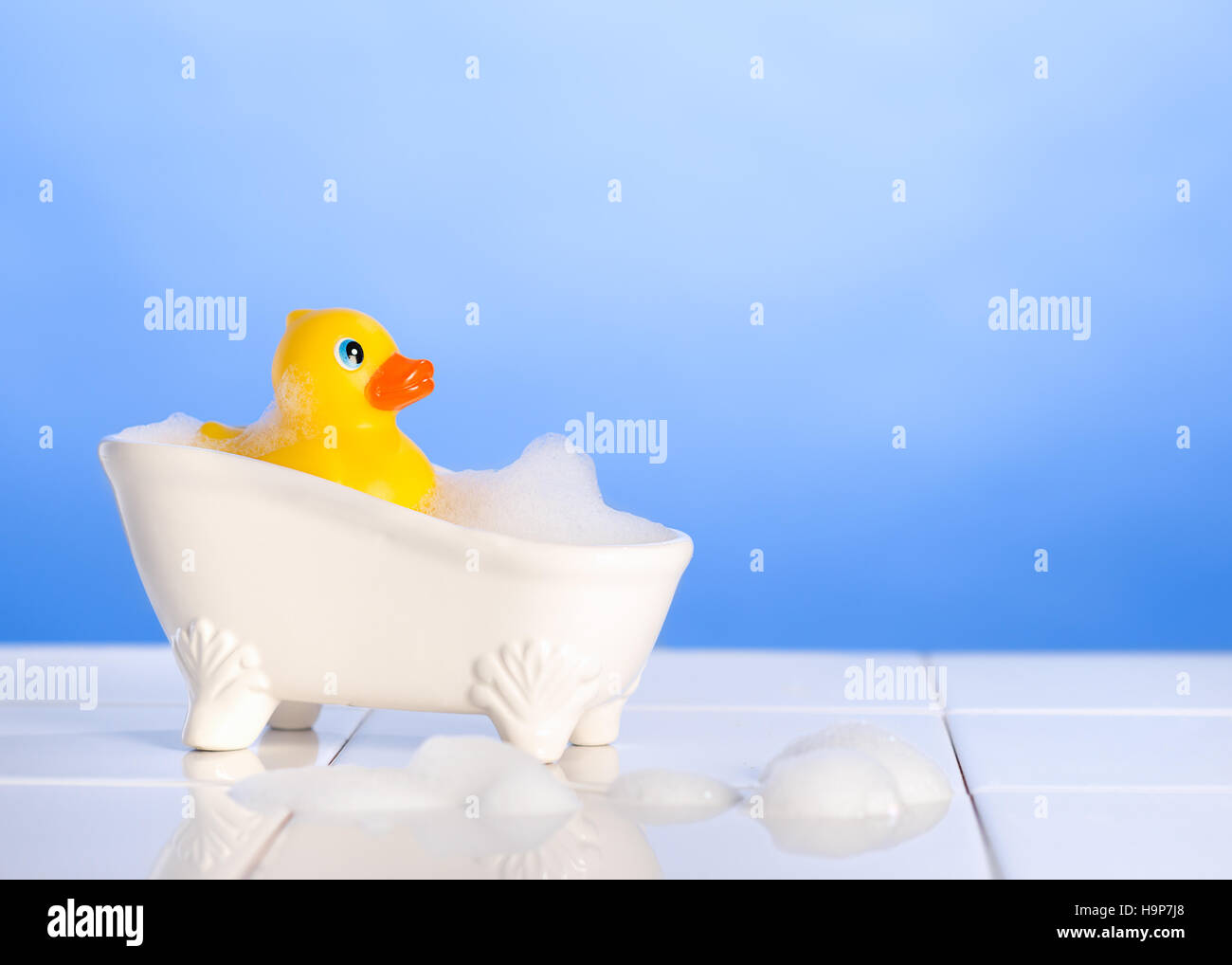 Rubber duck in the bath with soap suds on a blue background - Stock Image