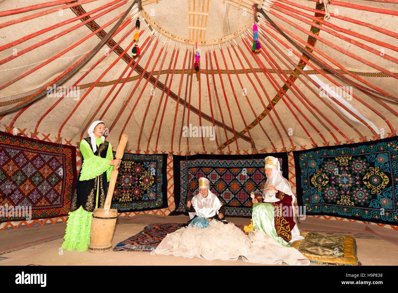 Kazakh women beating and spinning the wool, Kazakh ethnographical village Aul Gunny, Talgar city, Almaty, Kazakhstan - Stock Image