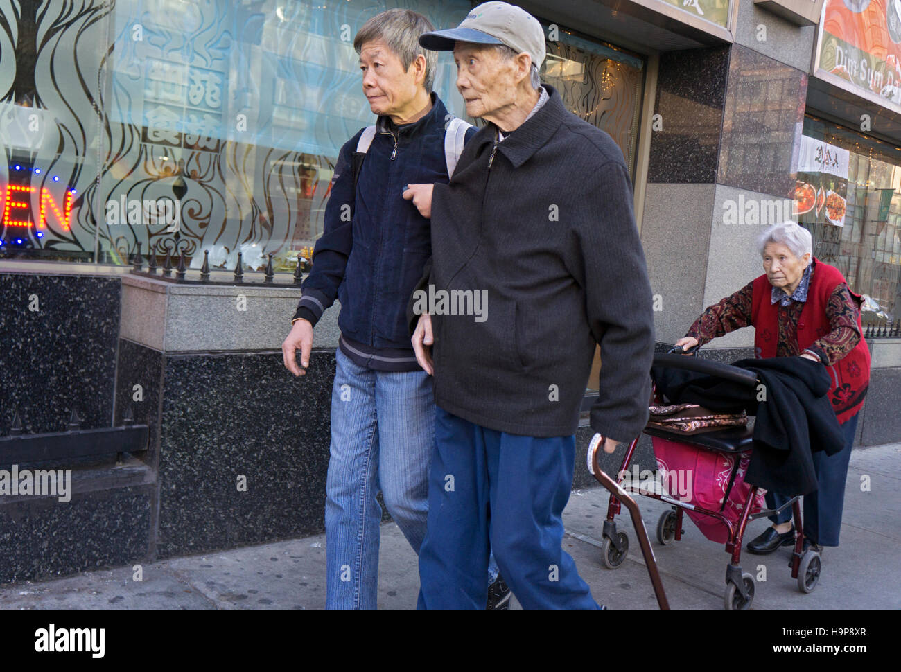 3 elderly Asian Americans walking in Chinatown, downtown Flushing, Queens, New York City - Stock Image