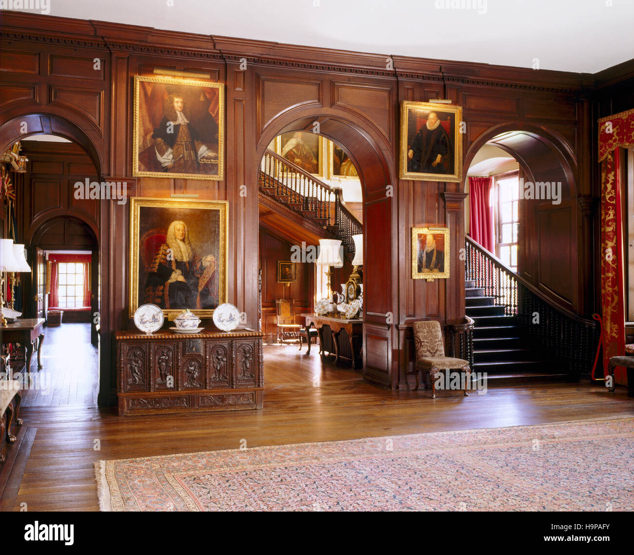 View of the entrance Hall at Antony showing the staircase, three arches , stained oak panelling, paintings and early - Stock Image