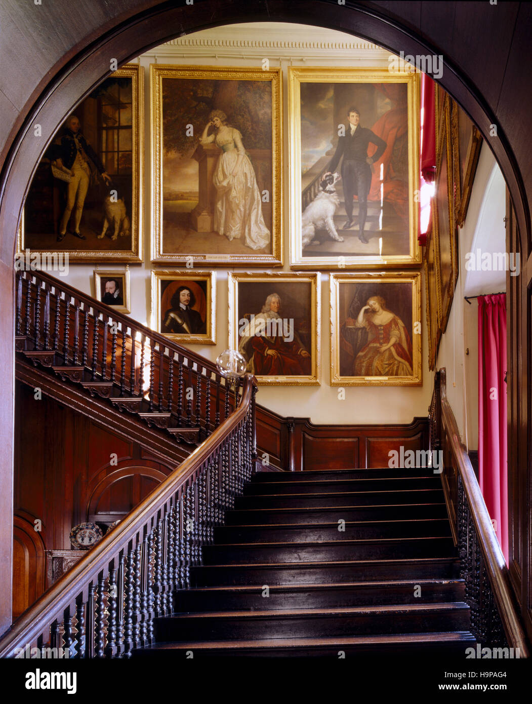 Entrance Hall at Antony House showing the staircase with portraits , oak banisters, and arch. - Stock Image