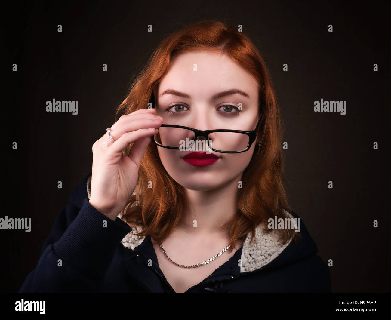 Beautiful nerd girl or young woman looking over eyeglasses. Vision, skepticism, evaluation, seduction, education - Stock Image