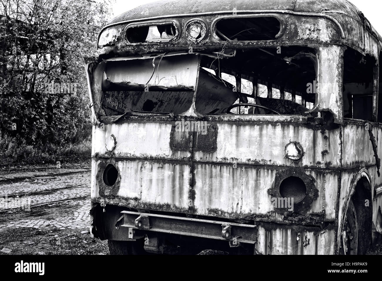Old abandoned bus wreck. Black and white photo - Stock Image