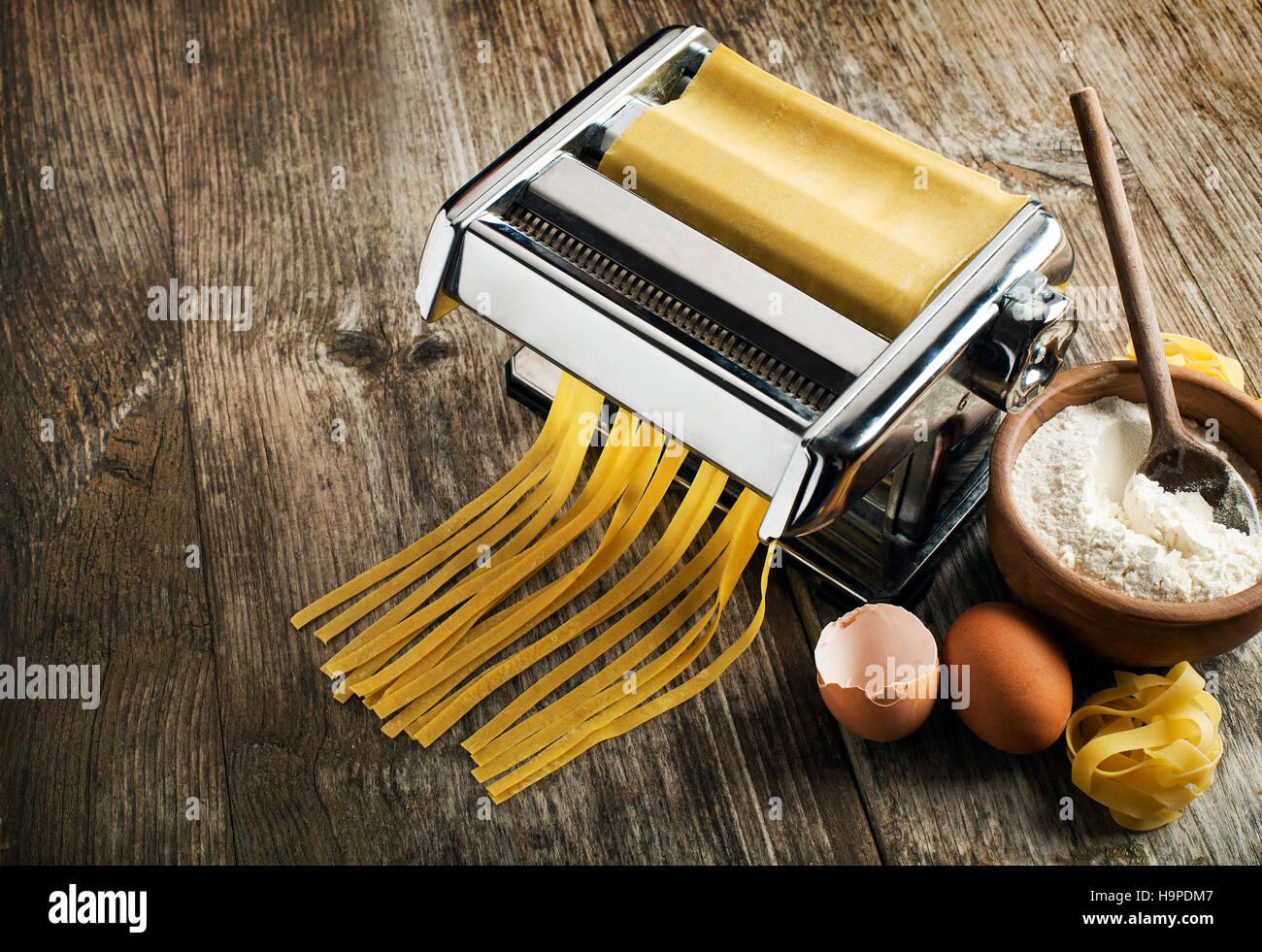 Fresh pasta making in machine on wooden background - Stock Image
