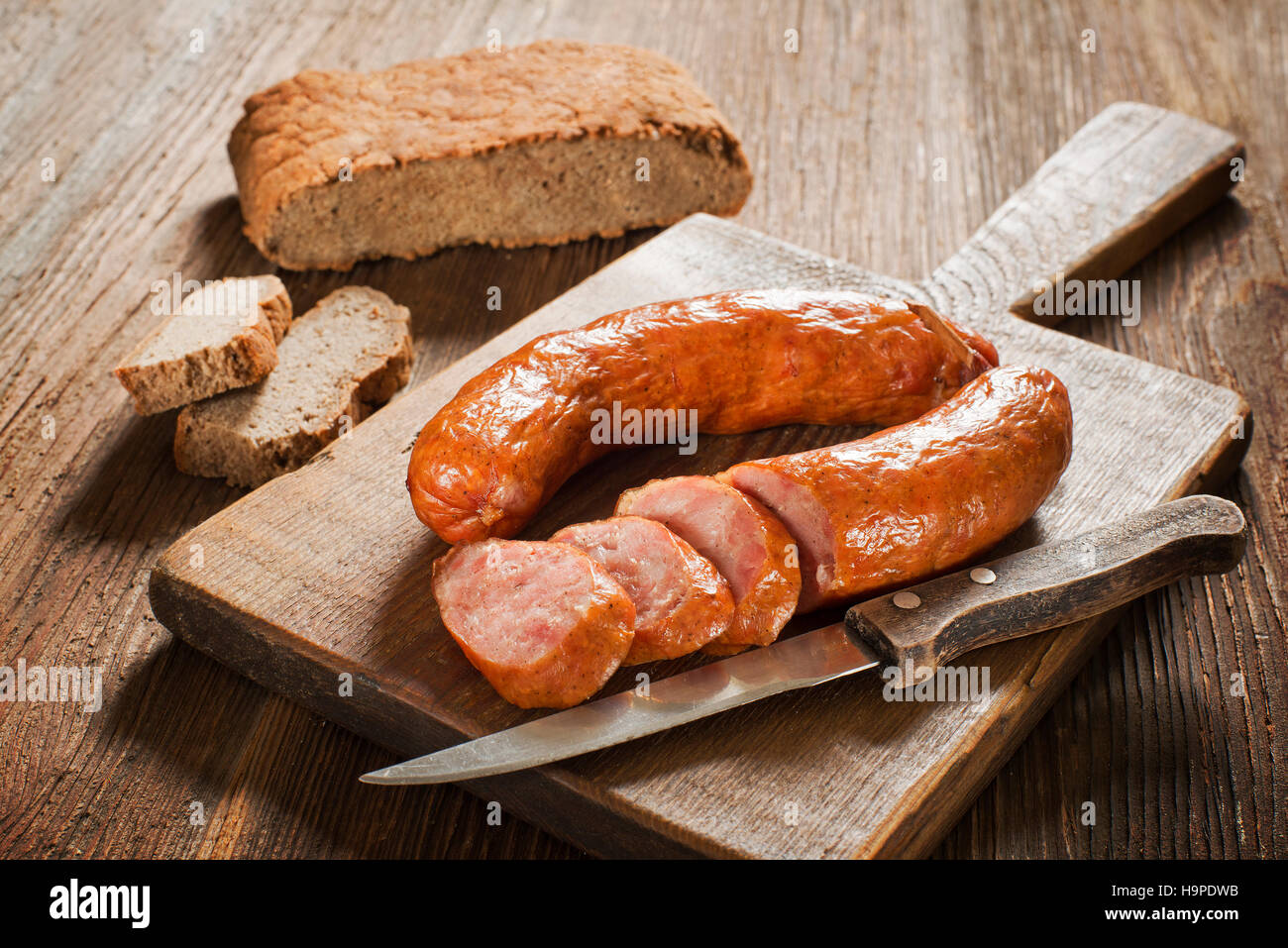 the sliced tasty sausage with bread on the wooden table - Stock Image
