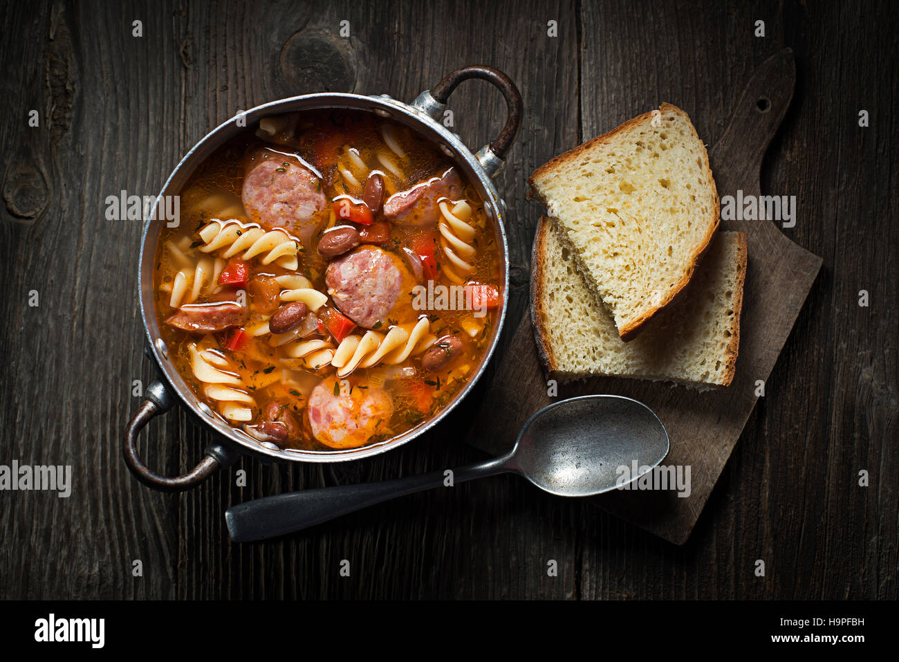 Fresh bean stew with sausage and pasta on wooden background - Stock Image