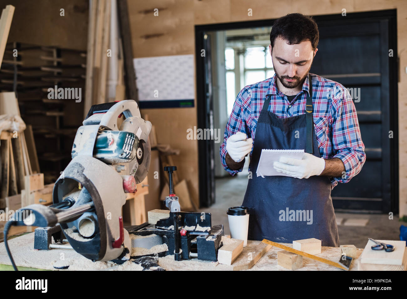 Carpenter taking a coffee break holding notebook in front of circular saw at his workshop - Stock Image