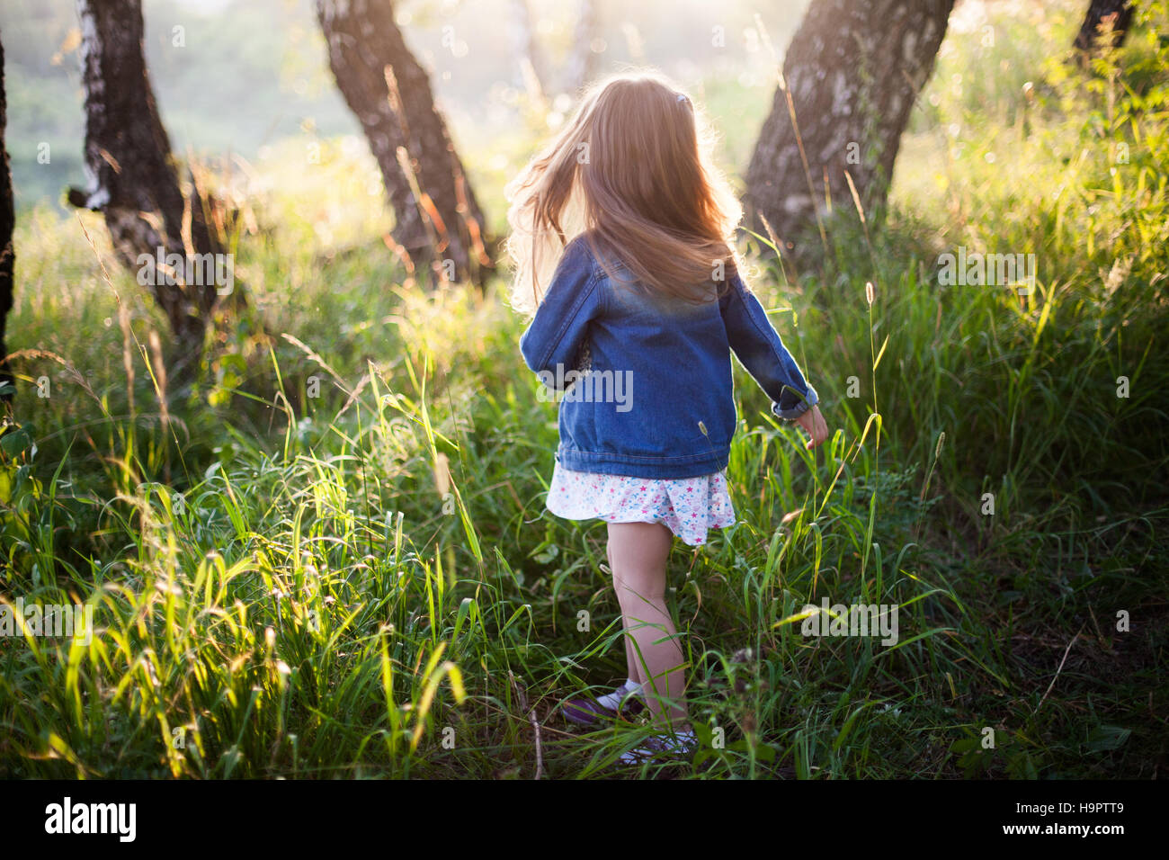 Little girl with long hair running, meadow, sunset - Stock Image