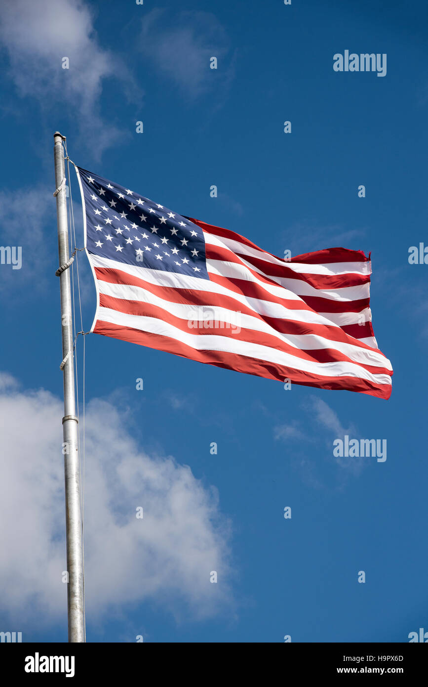 Stars and Stripes flag flying from a flagpole on a breezy day - USA - Stock Image