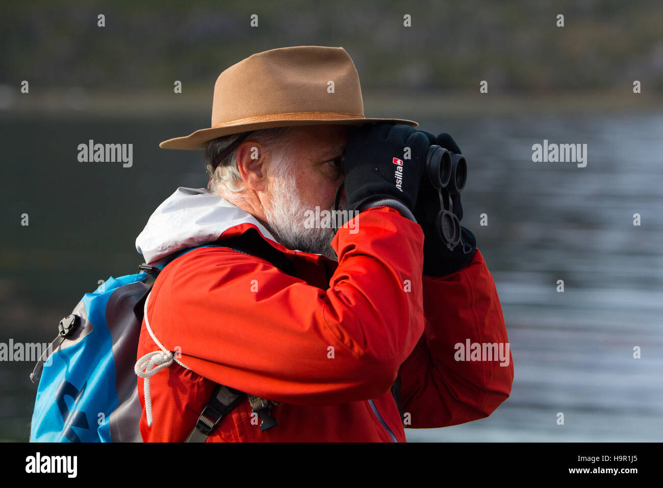 A nature tourist looking through his binoculars at birds wearing a bright red coat - Stock Image