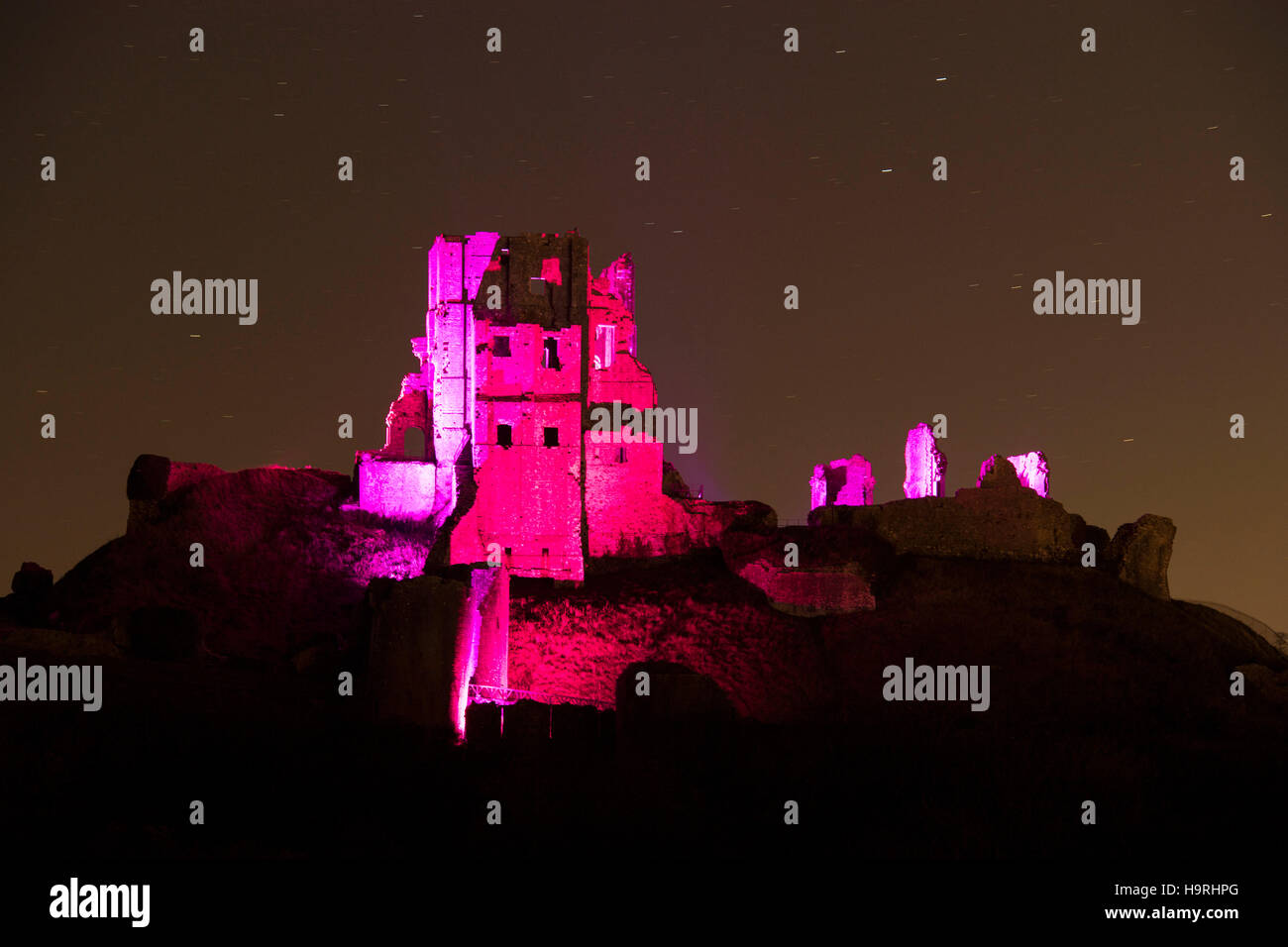 Corfe Castle is lit up in purple to raise awareness of pancreatic cancer, Dorset, UK - Stock Image