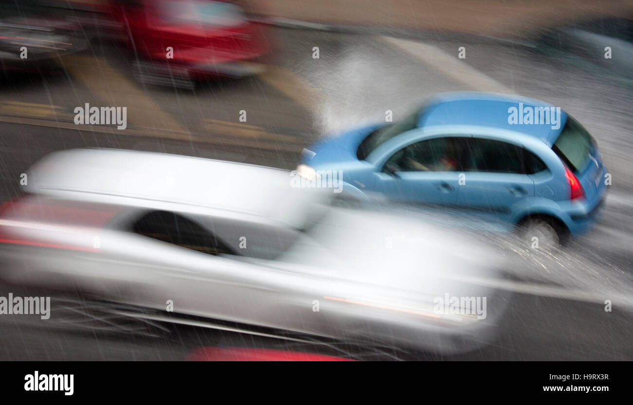 Driving cars in the city street hit by the heavy rain with hail in dangerous situation with low visibility and splashing - Stock Image
