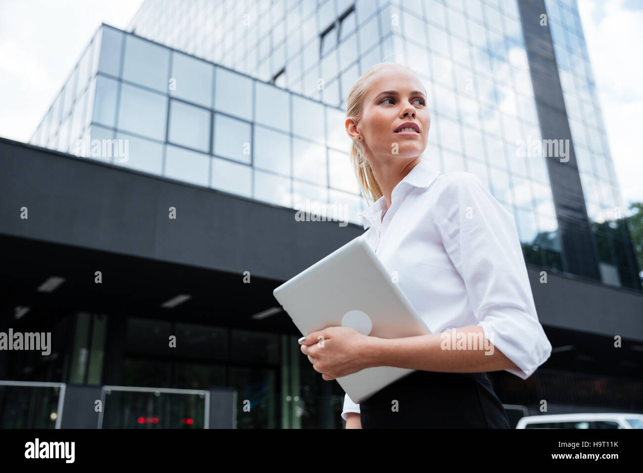 Business woman working with the tablet outdoors standing near the office - Stock Image