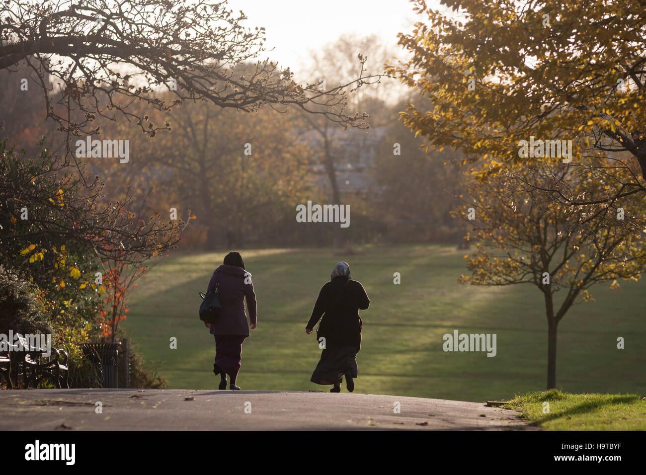 Two Muslim women walk through Brockwell Park in Herne Hill, Lambeth SE24 south London. - Stock Image