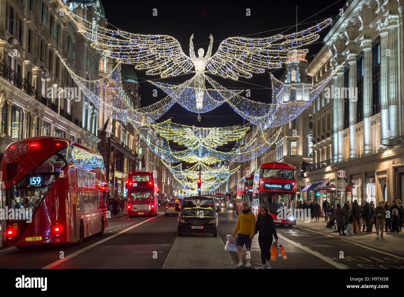 LONDON - NOVEMBER 18, 2016: Red double-decker bus pass under twinkling Christmas angels lighting up the upscale - Stock Image