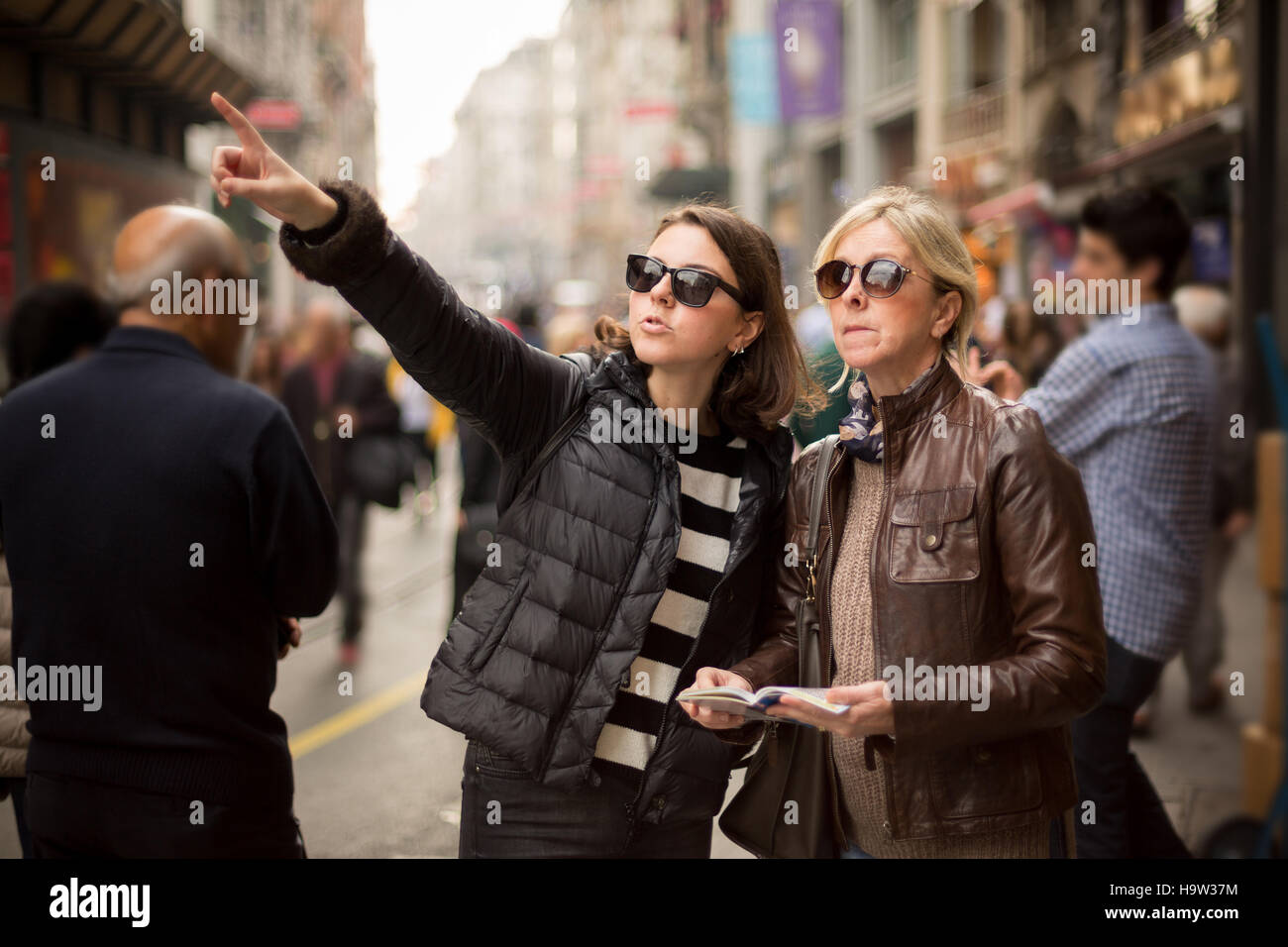 Mother and daughter are on the street and looking for a place to visit ,they are using a travel guide to explore - Stock Image