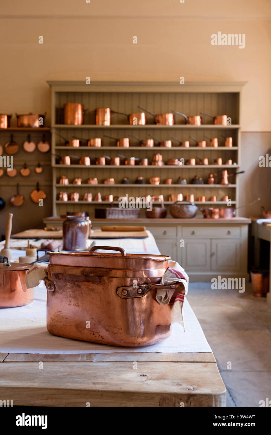 The Kitchen at Attingham Park, Shropshire. The elm-topped table and dresser are filled with the copper batterie - Stock Image